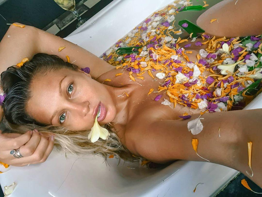 Lora, goală în cada plină cu petale de flori